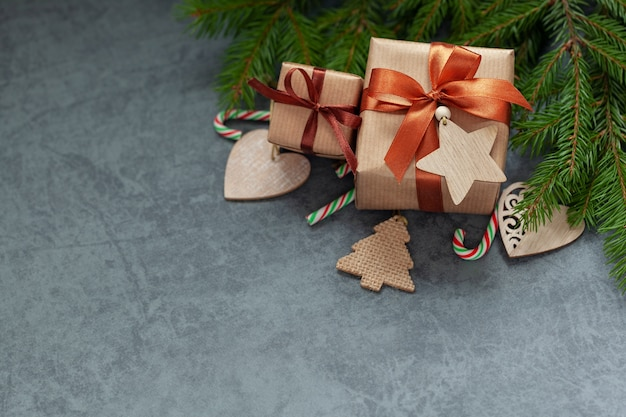 Two gifts wrapped craft paper with fir branches ongray background