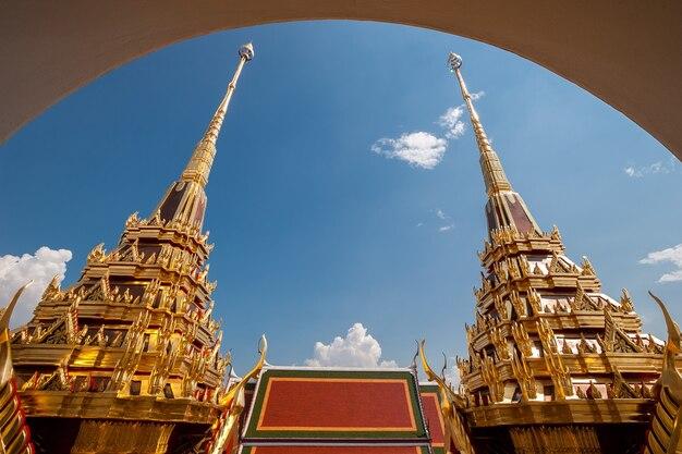 Две золоченые крыши храма с высокими шпилями и красивыми позолоченными деталями. вид через арку. небо с облаками.