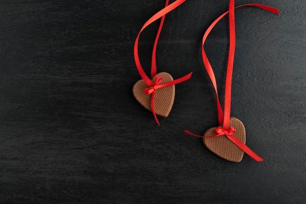 Украшение из двух имбирных печений на день святого валентина. печенье в форме сердца с красными лентами на черной поверхности.