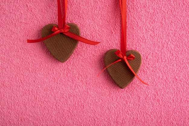 Two gingerbread cookies in shape of hearts on red ribbons on pink background. mothers day. womans day. valentines day.