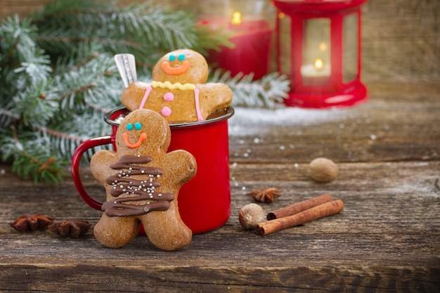 Two gingerbread men with mug of hot chocolate and glowing lantern on wooden