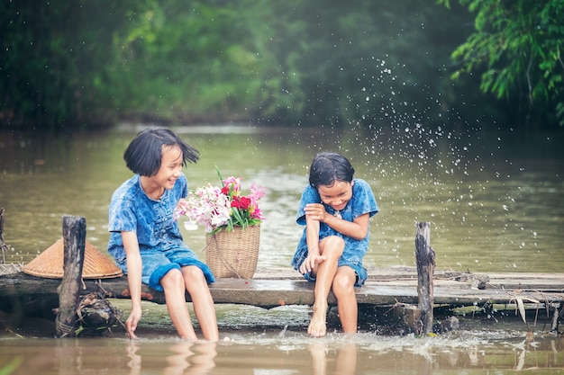 Two girl children sitting and playing water together on wooden bridge over swamp, asian ki