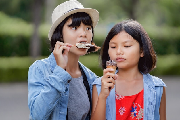 공원에서 여행을 걷는 동안 거리에서 아이스크림을 먹는 두 소녀