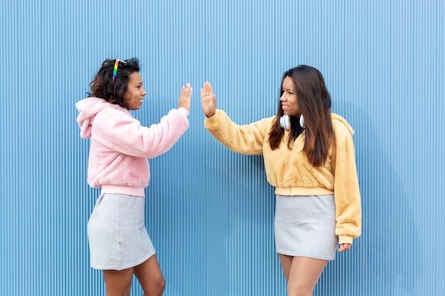 挨拶として手のひらをたたく2人のガールフレンド。彼らは青い壁に隔離されています。テキスト用のスペース。友情の概念。