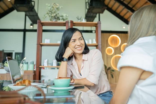Две подруги пьют кофе в кафе. две женщины в кафе, разговаривают, смеются и наслаждаются своим временем. концепции образа жизни и дружбы с реальными моделями людей.