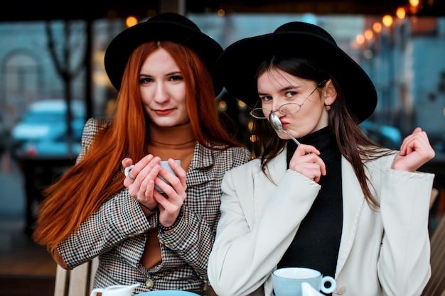 カフェでコーヒーを飲む2人のガールフレンド