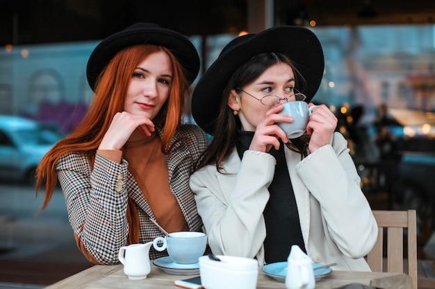 Две подруги пьют кофе в кафе