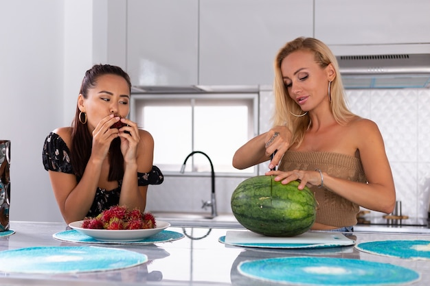 Two girl friends eating watermelon and rambutan tropical fruits in kitchen