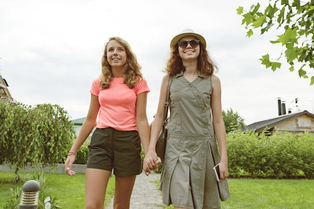 Two girl friends go holding hands