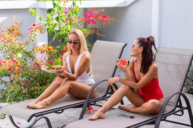 열대 국가에서 수박 휴일을 갖는 빌라에서 수영장에서 해변 의자에 수영복 아시아와 백인 두 여자 친구 신선한 과일