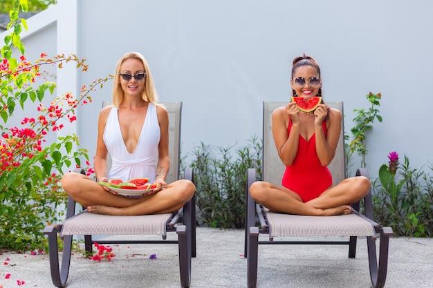 Две подруги в купальниках, азиатские и кавказские на шезлонге у бассейна на вилле, пьют арбуз отдых в тропических странах свежие фрукты