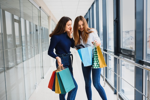ショッピングの2人のガールフレンドがバッグを持ってショッピングセンターを歩く