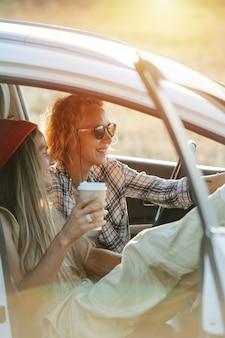 車の中で座って、草原の景色を楽しんでいる2人のガールフレンド。休憩、笑顔、印象の共有。