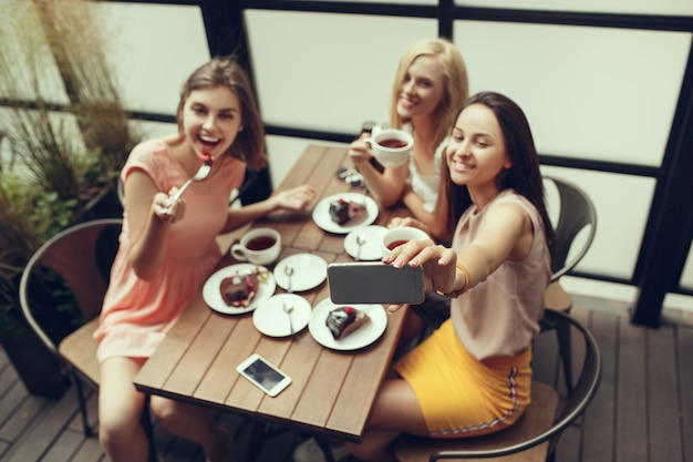 Two girl friends spend time together drinking coffee in the cafe, having breakfast and dessert.