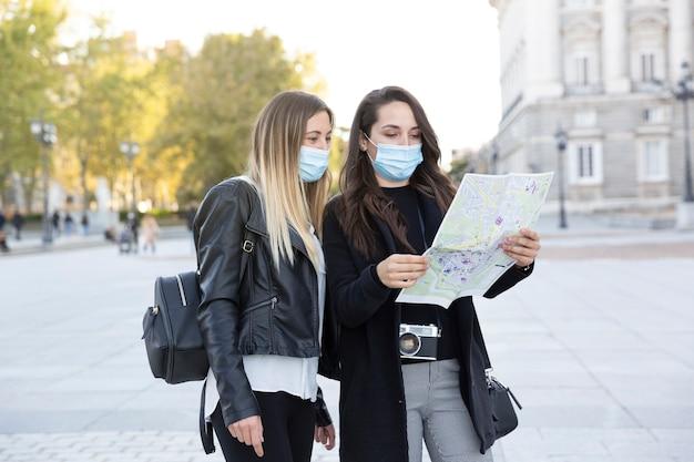 Две подруги, стоя в городе, глядя на туристическую карту. они в масках для лица. концепция нового нормального.