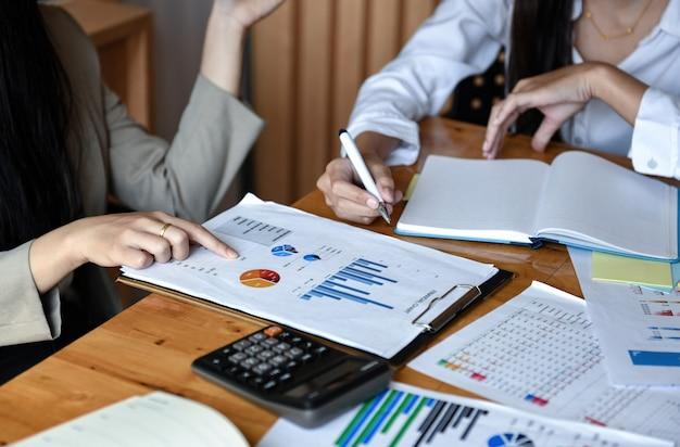 Две девушки офис анализируют графики на столе.