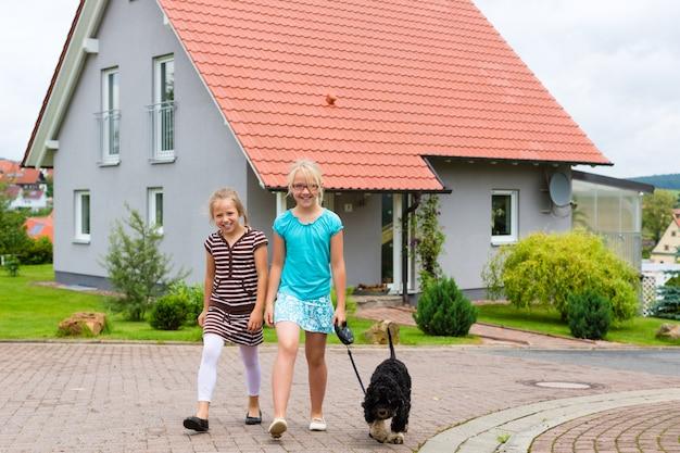 Две девочки или дети гуляют с собакой