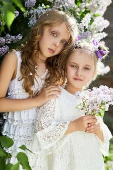두 소녀는 봄에 라일락 덤불에서 포즈를 취합니다. 태양 빛에 꽃에서 여자의 낭만적인 초상화