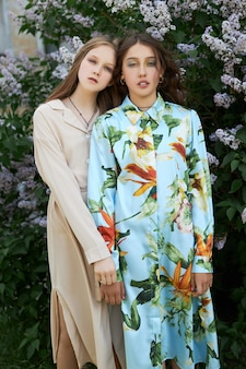 Two girl poses in a lilac bush in the spring. romantic portrait of a girls in flowers in the sun light