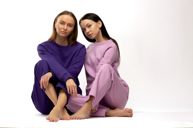Two girl in  sitting on the floor simple posing in similar clothing on studio white background