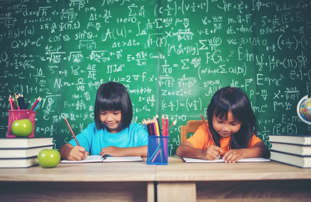 Two girl with crayon drawing at lesson in the classroom
