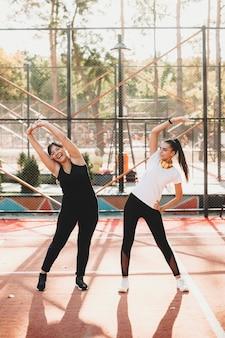 Две подруги делают растяжку перед кардио для похудения на открытом воздухе в спортивном парке утром.