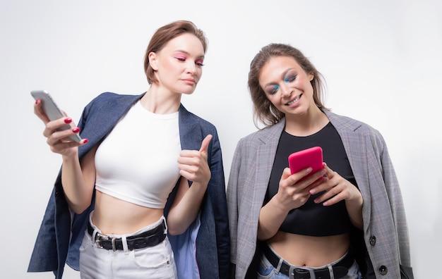 Две подруги переписываются на своих смартфонах и смеются. концепция блоггеров. сплетни. смешанная техника