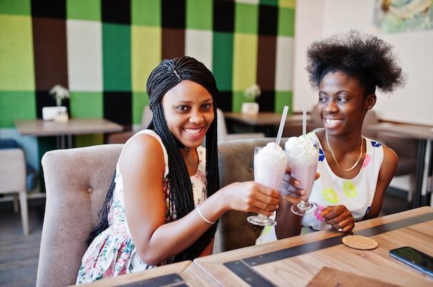 Две подружки в летних платьях пили коктейли молочного коктейля и аплодировали в кафе