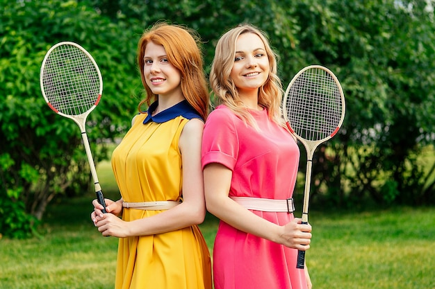 Two girlfriends beautiful young ginger redhead irish woman in a yellow dress and european blonde female person in a pink dress holding a tennis badminton racket in the summer park