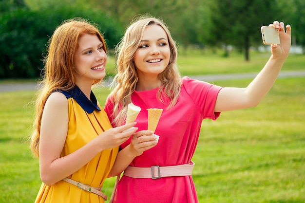 Two girlfriends beautiful young ginger redhead woman in a yellow dress and blonde female person in a pink dress eating vanilla ice cream in a waffle cone,in the summer park take picture selfie phone.