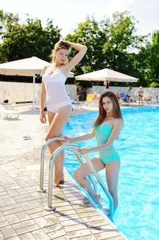 Two girlfriends in bikinis posing on a pool