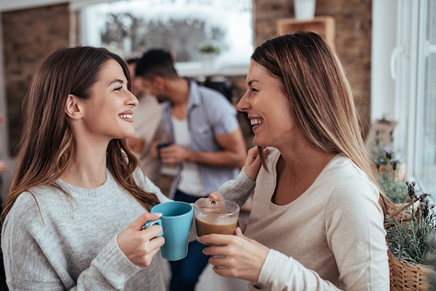 Two girlfriends in casual outfit talking and drinking tea and coffee.
