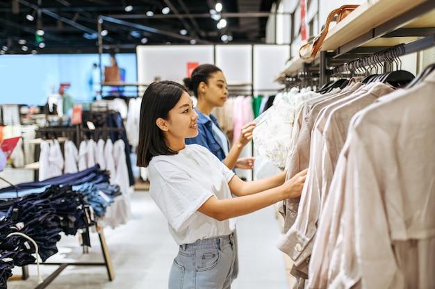 衣料品店で洋服を選ぶ2人のガールフレンド