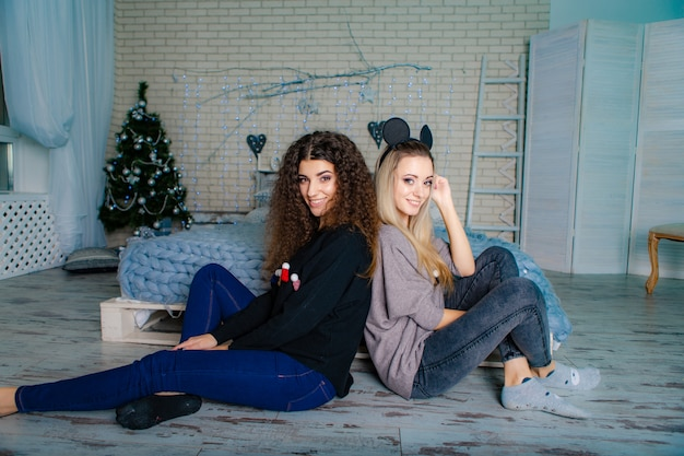 Two girlfriends in christmas sweaters sit with their backs to each other on the floor.