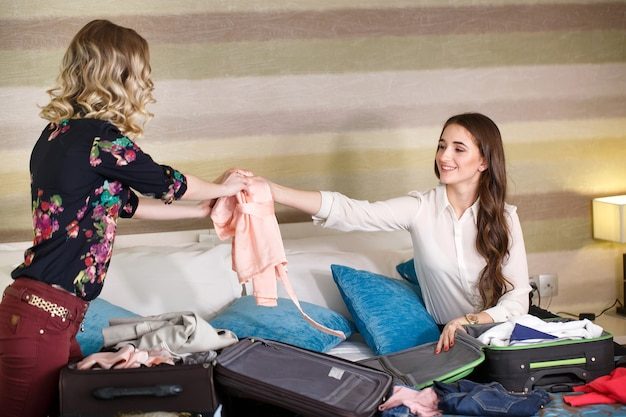 Two girlfriends collect a suitcase in a hotel room