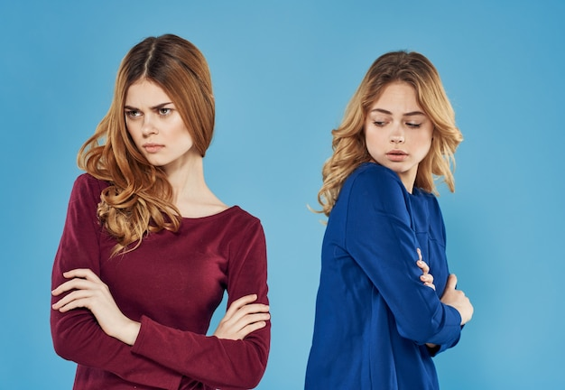 Two girlfriends in dress conflict emotions blue background studio. high quality photo