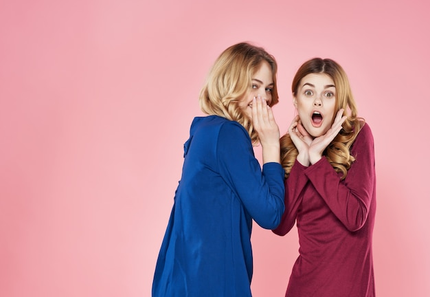 Two girlfriends in dresses are standing next to communication pink background