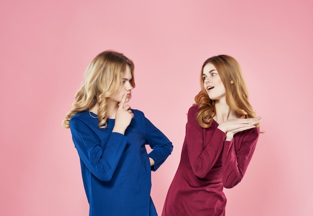 Two girlfriends dresses stand next to emotions displeasure pink background