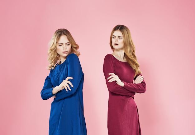 두 여자 친구 드레스는 감정 불쾌 분홍색 배경 옆에 서 있습니다. 고품질 사진