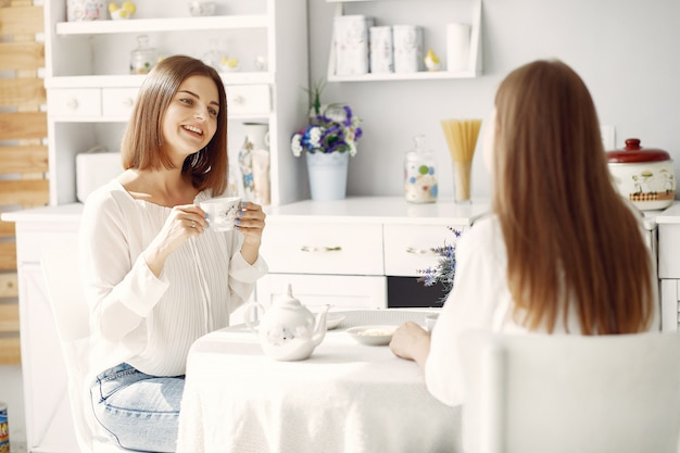 Две подруги пьют чай дома