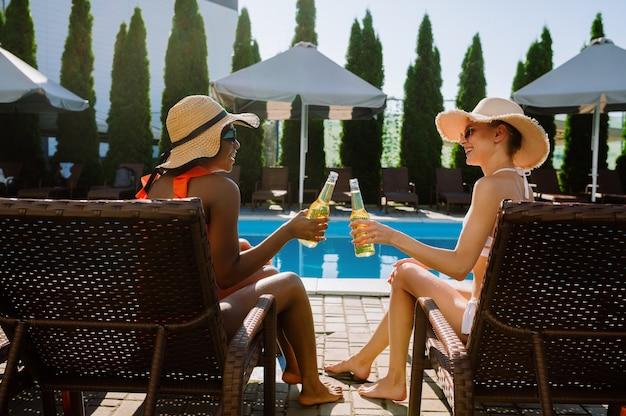 두 여자 친구는 수영장의 일광욕 침대에서 맥주를 마신다. 여름 방학에 즐거운 시간을 보내는 행복한 사람들, 야외 수영장에서 휴가 파티. 리조트에서 여성 레저