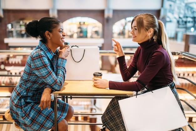 Две подруги пьют кофе в фуд-корте после покупок.
