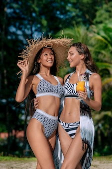 Two girlfriends in a fashion bikini relaxing beach and drinking fresh juice.  fashion style, trends youth, modern idea clothing leisure. sports tanned figures women