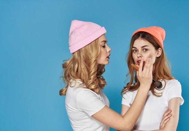 Две подруги модная одежда косметика досуг мода синий фон