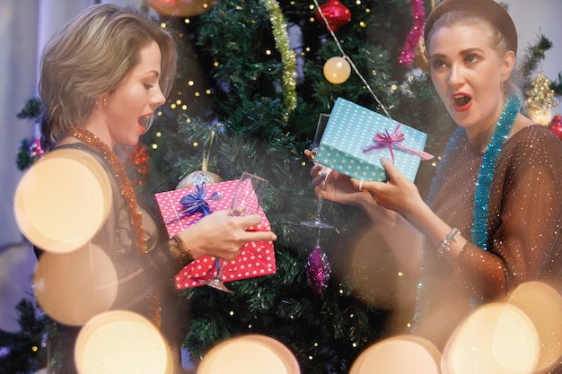 Two girlfriends give gift boxes to each other near a christmas tree.