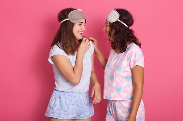 Две подруги сплетничают у розовой стены