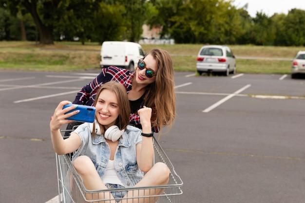 スーパーマーケットの駐車場で楽しい2つのガールフレンド。