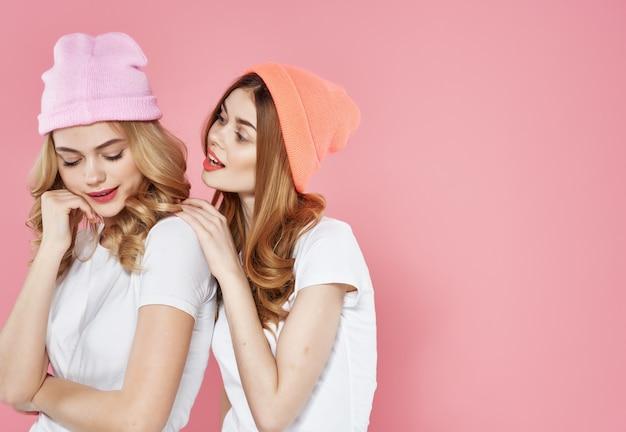 2人のガールフレンドがコミュニケーションの楽しいピンクの背景を抱きしめます