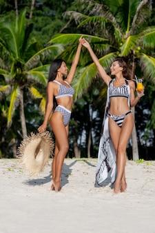 패션 비키니 입은 두 여자 친구가 서로의 손을 잡고 해변에서 휴식