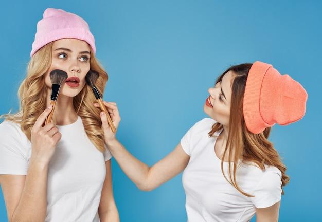 ファッショナブルな服の化粧品コミュニケーションライフスタイルエンターテインメント青い背景の2人のガールフレンド。高品質の写真